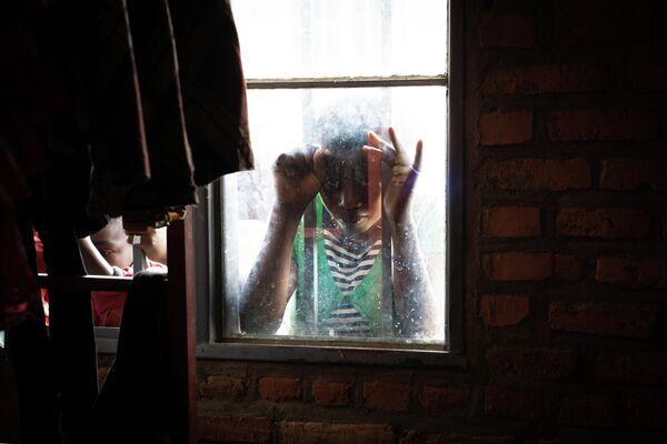 Девушка смотрит в окно транзитного центра Nyarushishi в Западной Руанде