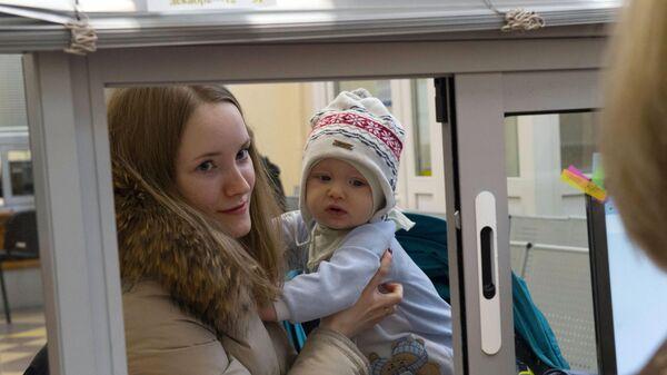 Молодая женщина с ребенком получает консультацию у сотрудницы центра занятости