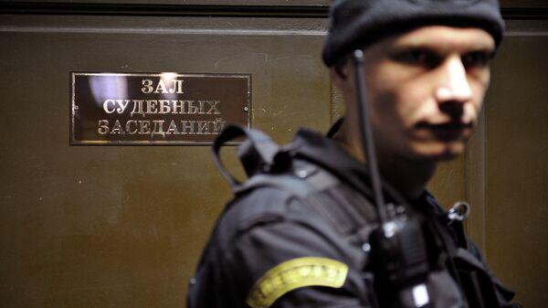 Сотрудник правоохранительных органов у входа в зал судебных заседаний