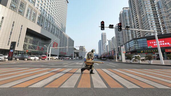 Рабочий с оборудованием для дезинфекции переходит дорогу у больницы в городе Ичан в китайской провинции Хубэй