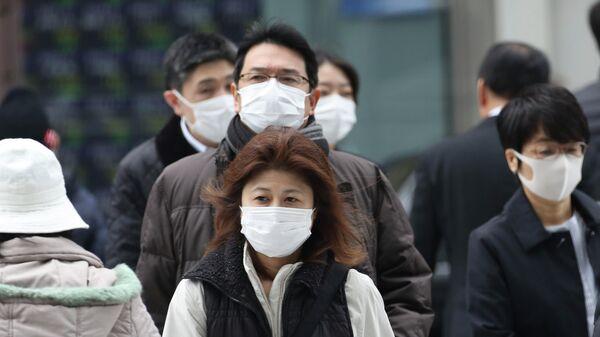 Прохожие в защитных масках на улице Токио, Япония. 17 февраля 2020