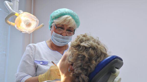 Врач-стоматолог во время приема пациента в городской стоматологической поликлинике