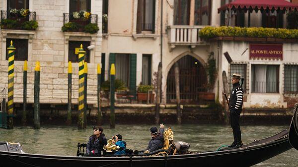 Туристы катаются в гондоле по каналам Венеции