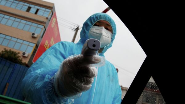 Медицинский работник с термометром на контрольно-пропускном пункте в Китае