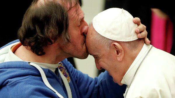 Мужчина целует папу Франциска во время еженедельной аудиенции в Ватикане