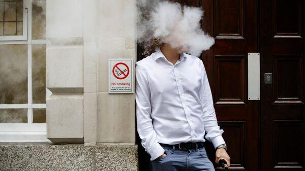 Мужчина курит электронную сигарету