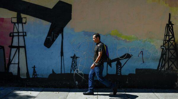 Мужчина проходит мимо граффити с изображением нефтяной вышки в Каракасе, Венесуэла