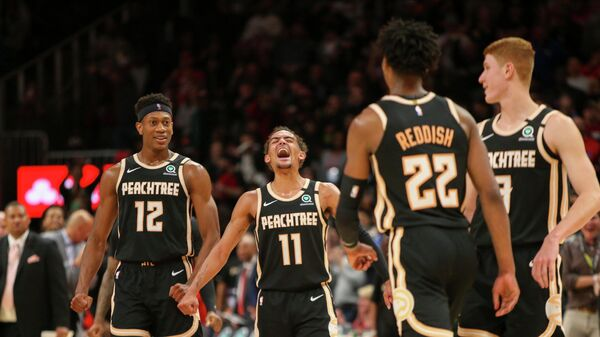Feb 20, 2020; Atlanta, Georgia, USA; Atlanta Hawks guard Trae Young (11) celebrates with forward De'Andre Hunter (12) and guard Kevin Huerter (3) after a basket by guard Cam Reddish (22) against the Miami Heat in the second half at State Farm Arena. Mandatory Credit: Brett Davis-USA TODAY Sports