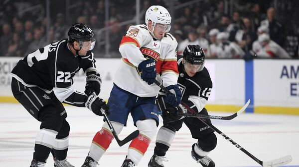 LOS ANGELES, CALIFORNIA - FEBRUARY 20: Frank Vatrano #77 of the Florida Panthers splits the defense of Trevor Lewis #22 and Trevor Moore #12 of the Los Angeles Kings during the first period at Staples Center on February 20, 2020 in Los Angeles, California.   Harry How/Getty Images/AFP