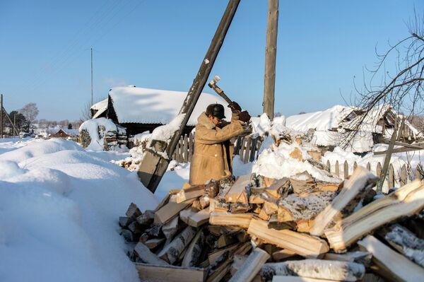 Мужчина колет дрова в селе Омской области