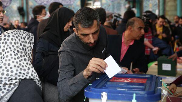 Мужчина во время голосования на парламентских выборов в Тегеране