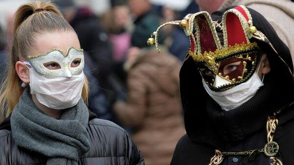 Участники карнавала в Венеции в защитных масках