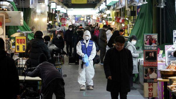 Сотрудник компании, занимающейся дезинфекцией, очищает пол на рынке в Сеуле, Южная Корея. 24 февраля 2020