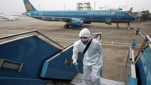 Работник распыляет дезинфицирующее средство на трапе самолета Вьетнамских авиалинии для защиты от недавней вспышки коронавируса в аэропорту Ной Бай в Ханое, Вьетнам