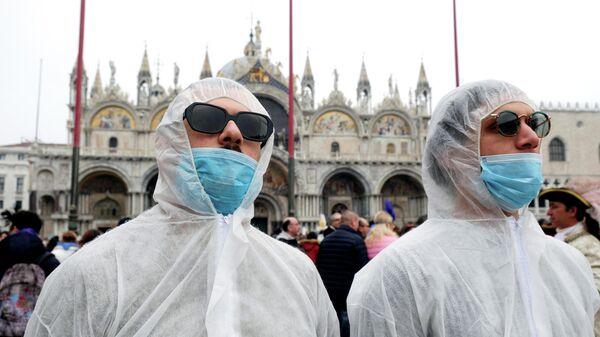 Туристы в защитных костюмах и масках во время карнавала в Венеции
