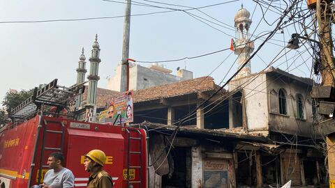 Пожарные около сгоревшей мечети в Нью-Дели