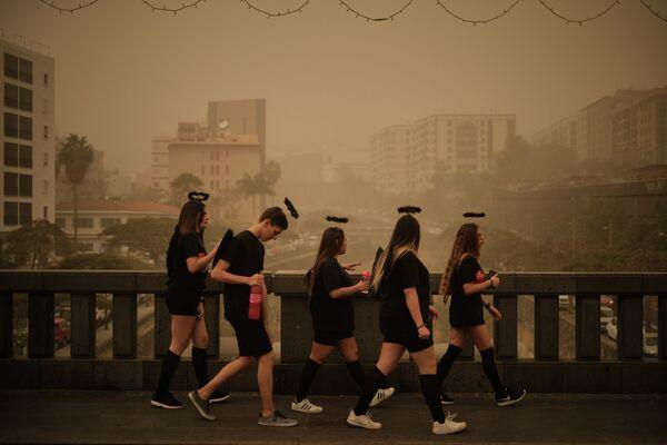 Участники карнавала переходят мост во время песчаной бури в Санта-Крус-де-Тенерифе, Испания