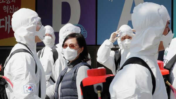 Южнокорейские военные в защитном снаряжении дезинфицируют город Дэгу