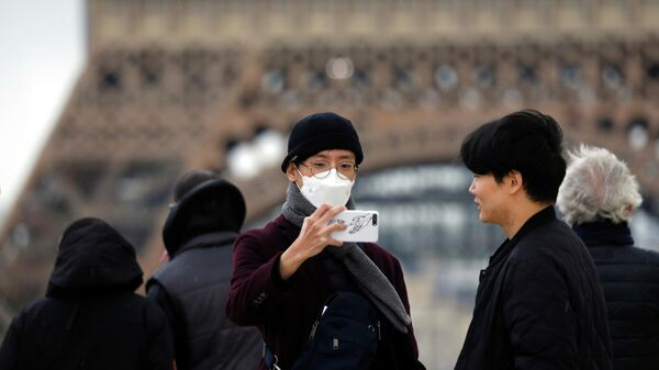 Туристы фотографируются на фоне Эйфелевой башни в Париже