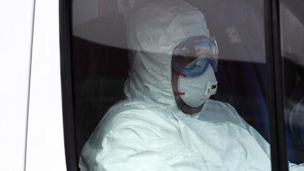 Медицинский работник в защитном костюме в машине скорой помощи возле территории больничного комплекса в Коммунарке