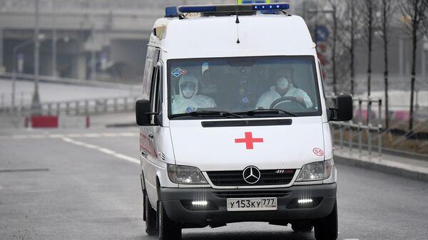 Медицинские работники в защитных костюмах в машине скорой помощи
