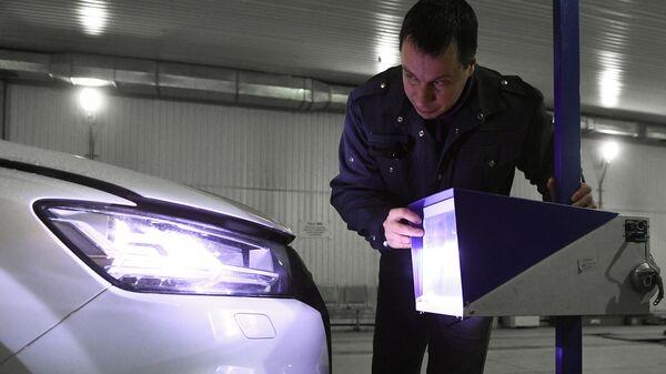 Технический эксперт проводит осмотр автомобиля на пункте техосмотра в Новосибирске