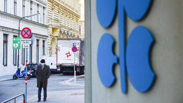 Мужчина в медицинской маске у штаб-квартиры Организации стран - экспортеров нефти (ОПЕК) в Вене