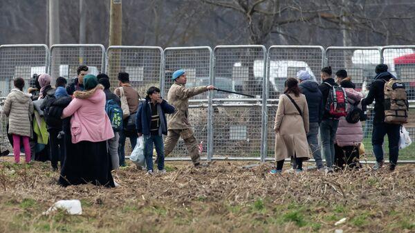 Турецкий военный и группа мигрантов в районе пограничного перехода Пазаркуле на границе Турции и Греции