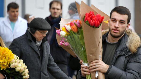 Покупатель с цветами на Рижском рынке в Москве