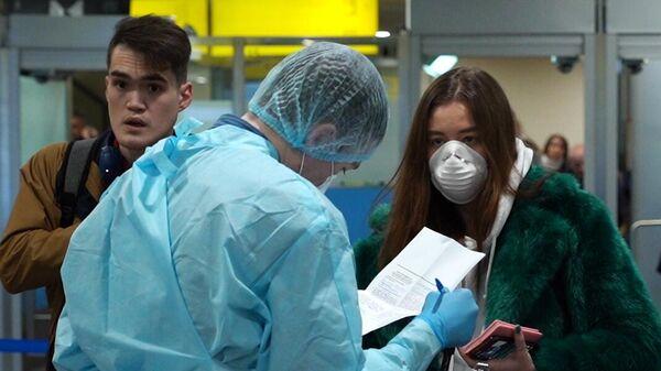 Медицинский работник проводит осмотр пассажиров в аэропорту Шереметьево