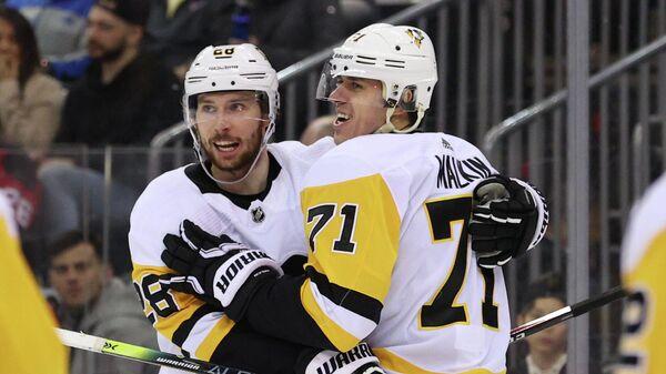 Хоккеисты Питтсбург Пингвинз Маркус Петерссон и Евгений Малкин празднуют гол в ворота Нью-Джерси Девилз в матче НХЛ