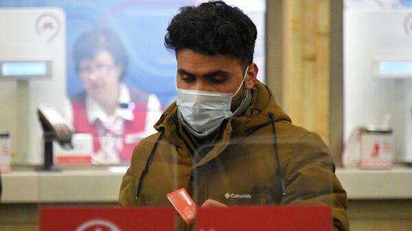 Мужчина в медицинской маске на одной из станций Московского метрополитена