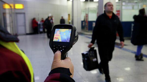 Сотрудник санитарно-эпидемиологической службы  Казахстана проверяет тепловизором температуру пассажиров в аэропорту Алма-Аты