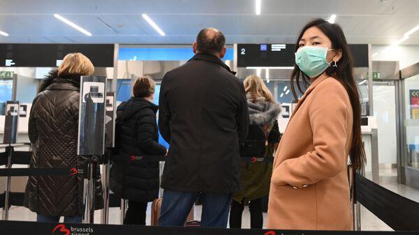 Пассажиры в медицинских масках в зоне регистрации в аэропорту Брюсселя