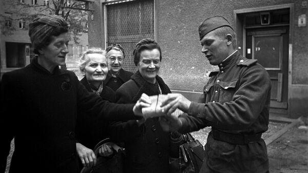 Советский солдат раздает хлеб женщинам Берлина