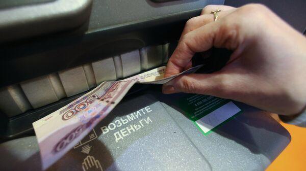 Женщина получает наличные деньги в банкомате