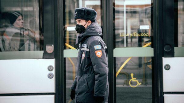 Полицейский в защитной маске на одной из улиц Нур-Султана