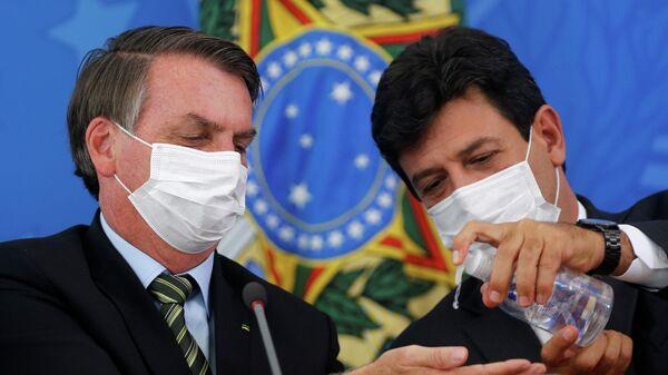 Президент Бразилии Жаир Болсонару и министр здравоохранения Луис Энрике Мандетта дезинфицируют руки во время пресс-конференции