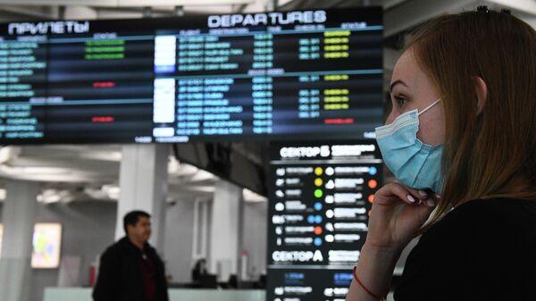 Девушка в медицинской маске в аэропорту Толмачево в Новосибирске