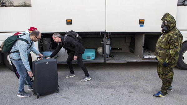 Российские туристы укладывают багаж в автобус на территории аэропорта Тиват в Черногории