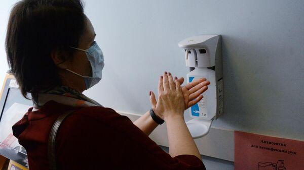 Пациент поликлиники №1 Владивостока дезинфицирует руки антисептиком перед тем как посетить кабинет врача