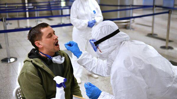 Медицинский работник проверяет состояние пассажира в аэропорту Внуково