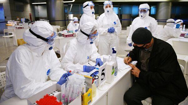 Медицинские работники проверяют состояние пассажиров в аэропорту Внуково