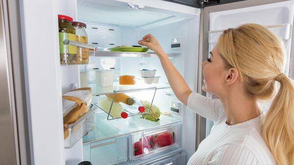 Девушка достает продукты из холодильника