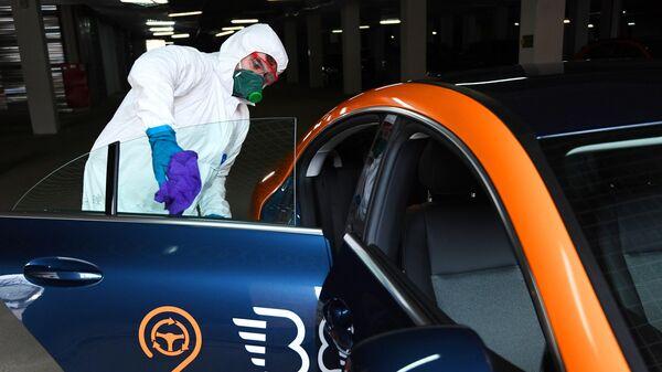 Сотрудник санитарной службы во время дезинфекции автомобиля сервиса каршеринга