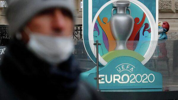 Человек в маске на фоне логотипа Евро-2020