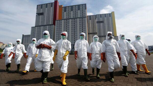 Сотрудники Индонезийского общества Красного Креста  во время операции по распылению дезинфицирующего средства в деревне для спортсменов Кемайора в Джакарте, Индонезия