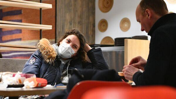 Девушка в защитной маске в кафе Макдональдс в Москве