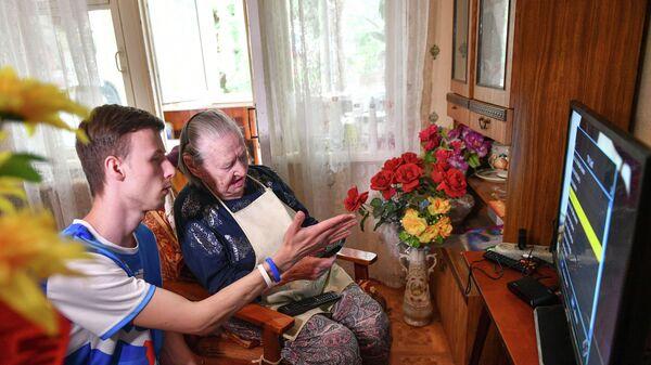 Волонтер помогает пожилой женщине в настройке телевизора