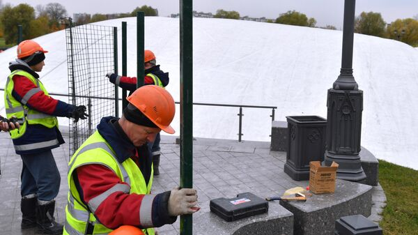 Рабочие устанавливают ограждение вокруг фонтана после демонтажа в парке Царицыно в Москве